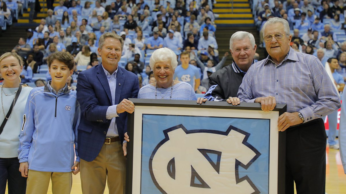 Stallings and Chancellor Guskiewicz hold a UNC banner in front of basketball fans