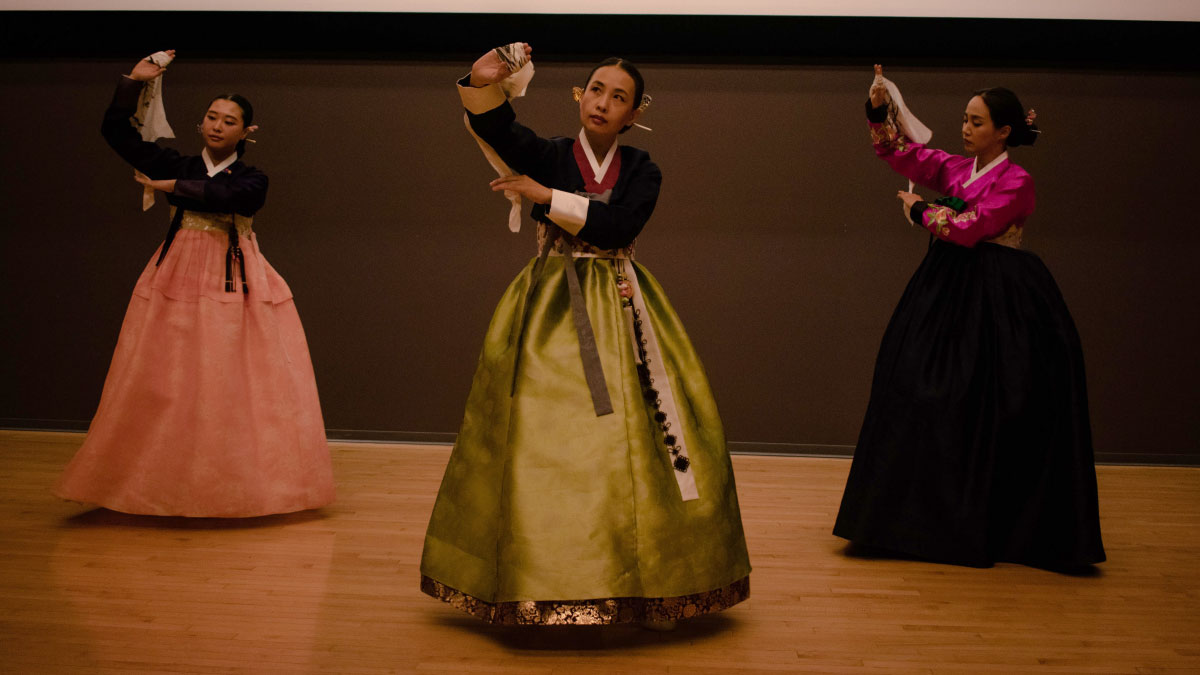 Three women dance in tradional Korean attire.