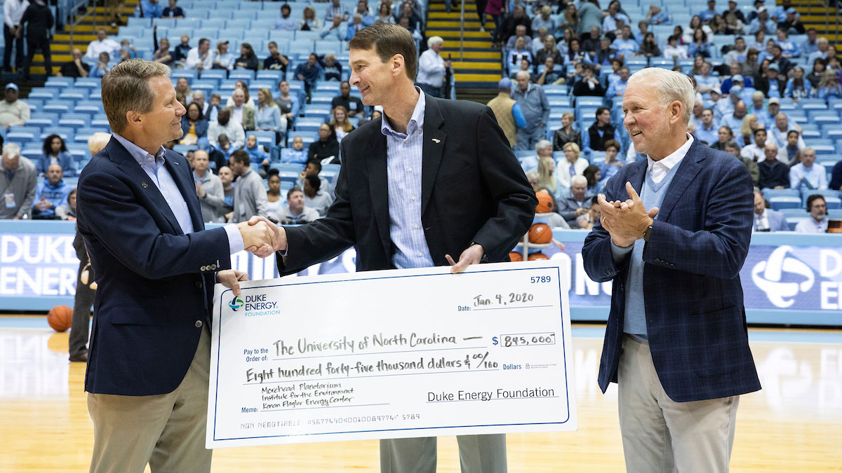 David Fountain hands an oversized check to Chancellor Kevin Guskiewicz and Vice Chancellor of Development David Routh.