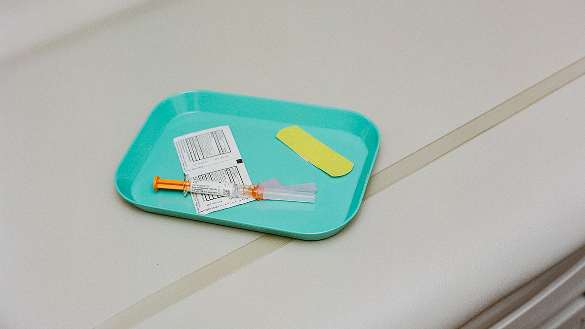 Vaccine on a tray with swabs and a band-aid.