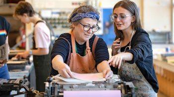 A professor teaches a student to use a letterpress machine.