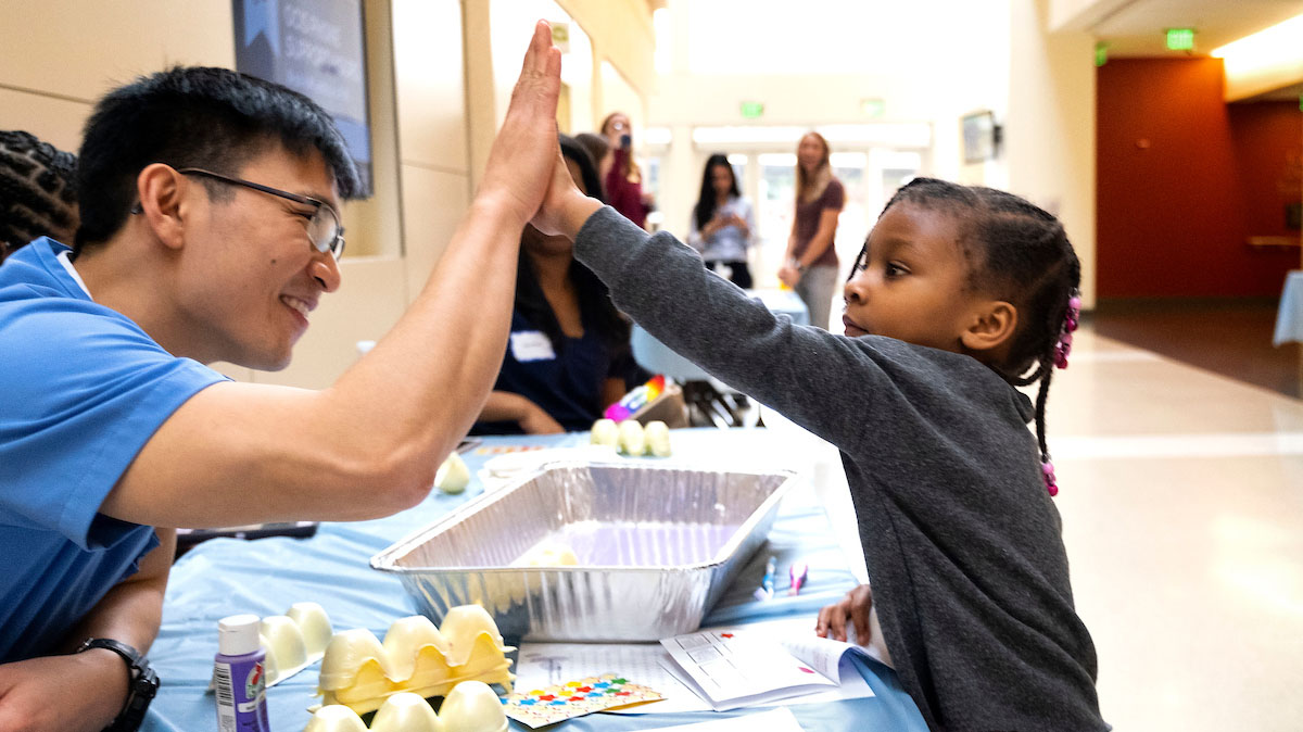 A male student gives a high five to a small child.