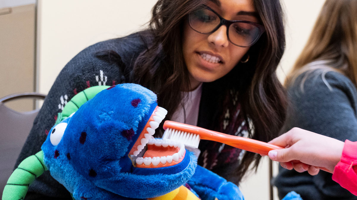 A women brushes the teeth of a stuffed toy.