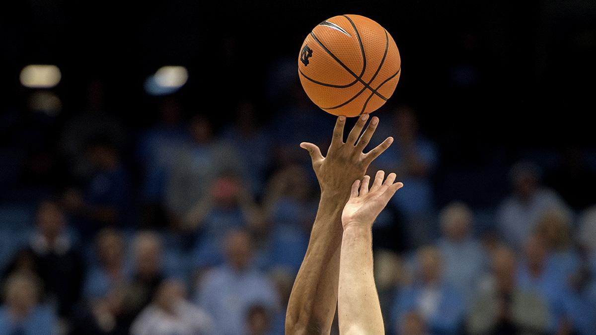 Two basketball players jump for a basketball.