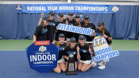 The women's tennis team holds of championship signs.