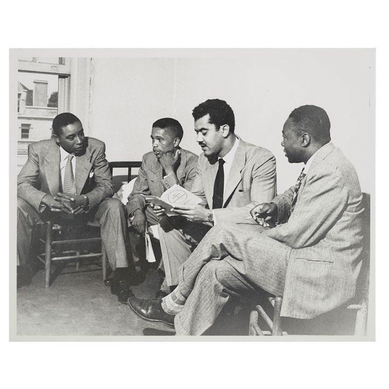 Four men sit in a dorm room.