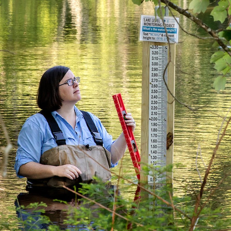 A women in a lake measures water depth.
