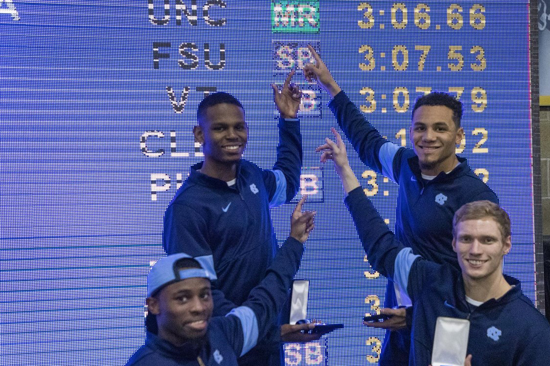 Ari Cogdell, Ryan Saint-Germain, Isaiah Palmer, Brandon Cachon stand in front of a scoreboard.