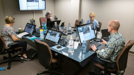 People sit around a table for a webinar.