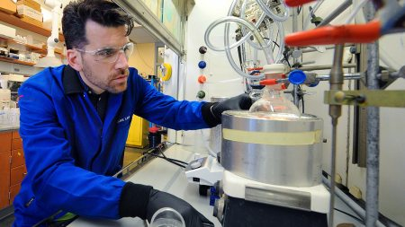 A man works with chemistry equipment.