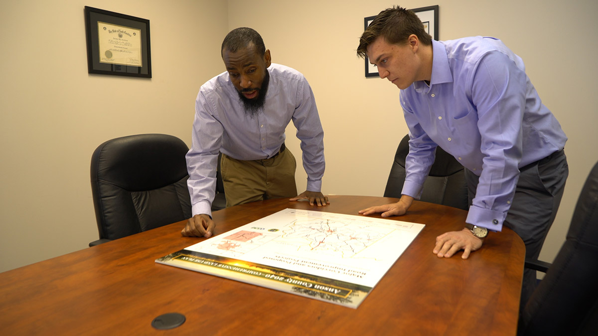 Two men look at a document on a table.