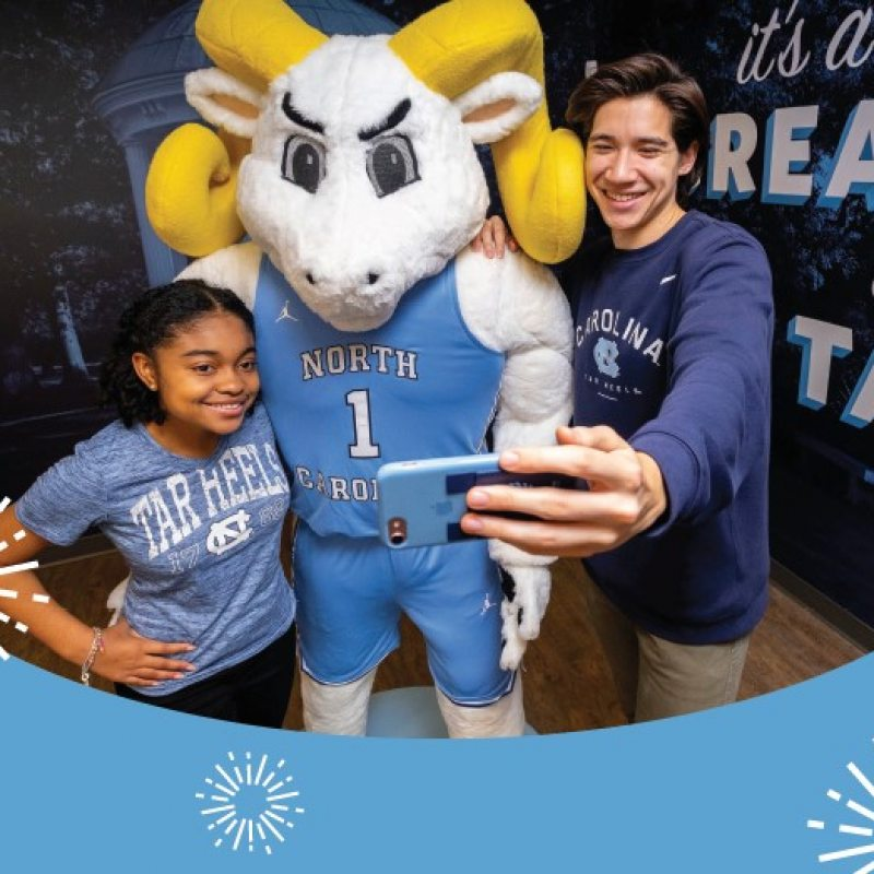 Two students take a selfie with Rameses.