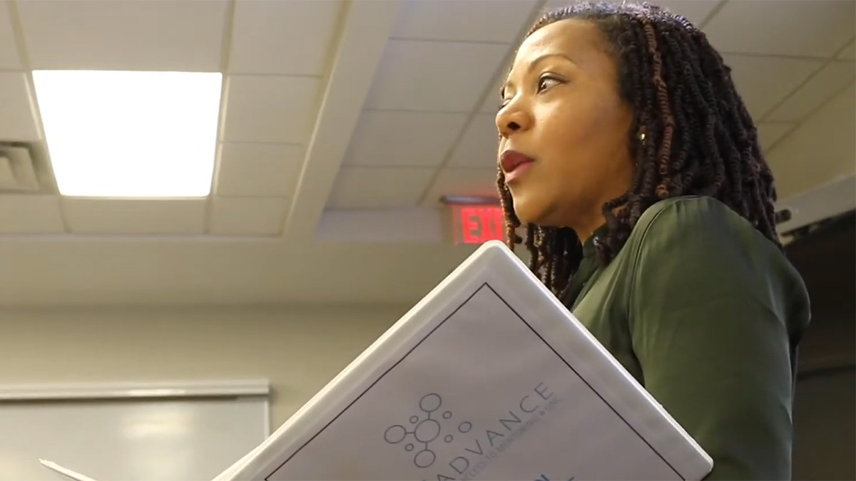 A woman holds a binder while talking to a class.