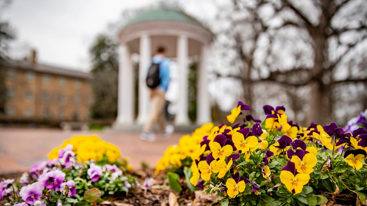 A student walks near the Old Well in front of flowers.