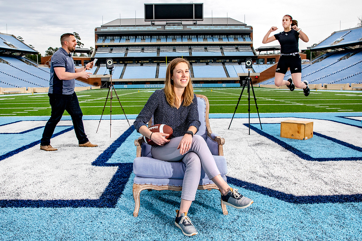 A woman sits on a chair on the field in Kenan Stadium with a person jumping behind her.