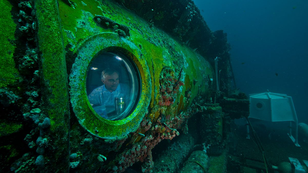 A man looks out of a window of a submarine.