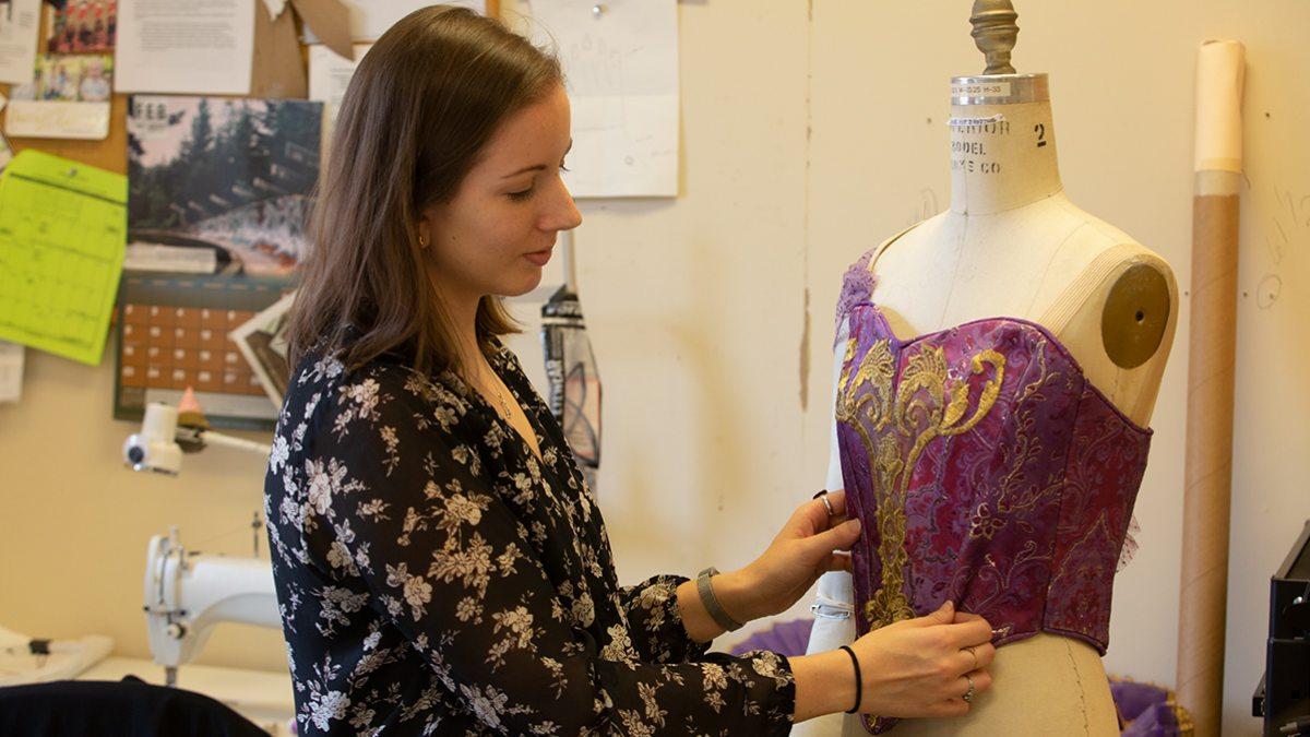 Jane Reichard adjusts a dress on a model.