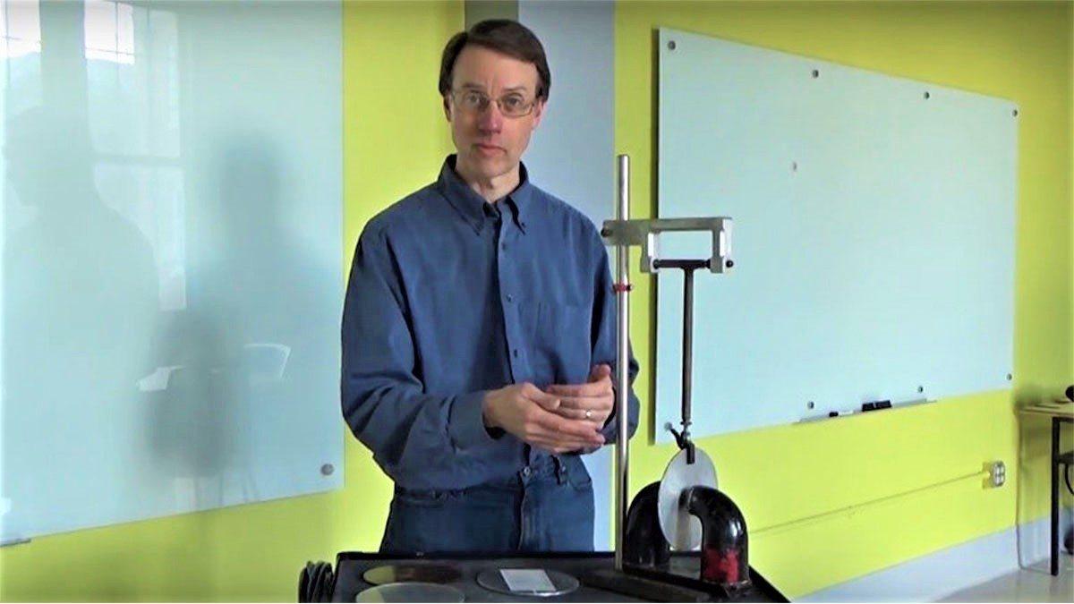 Duane Deardorff stands near a physics experiment.