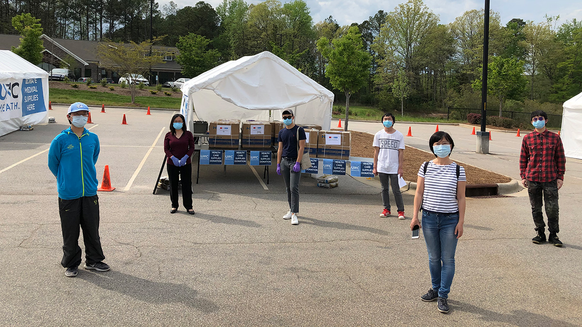 Five students wearing masks stand near boxes of medical masks.