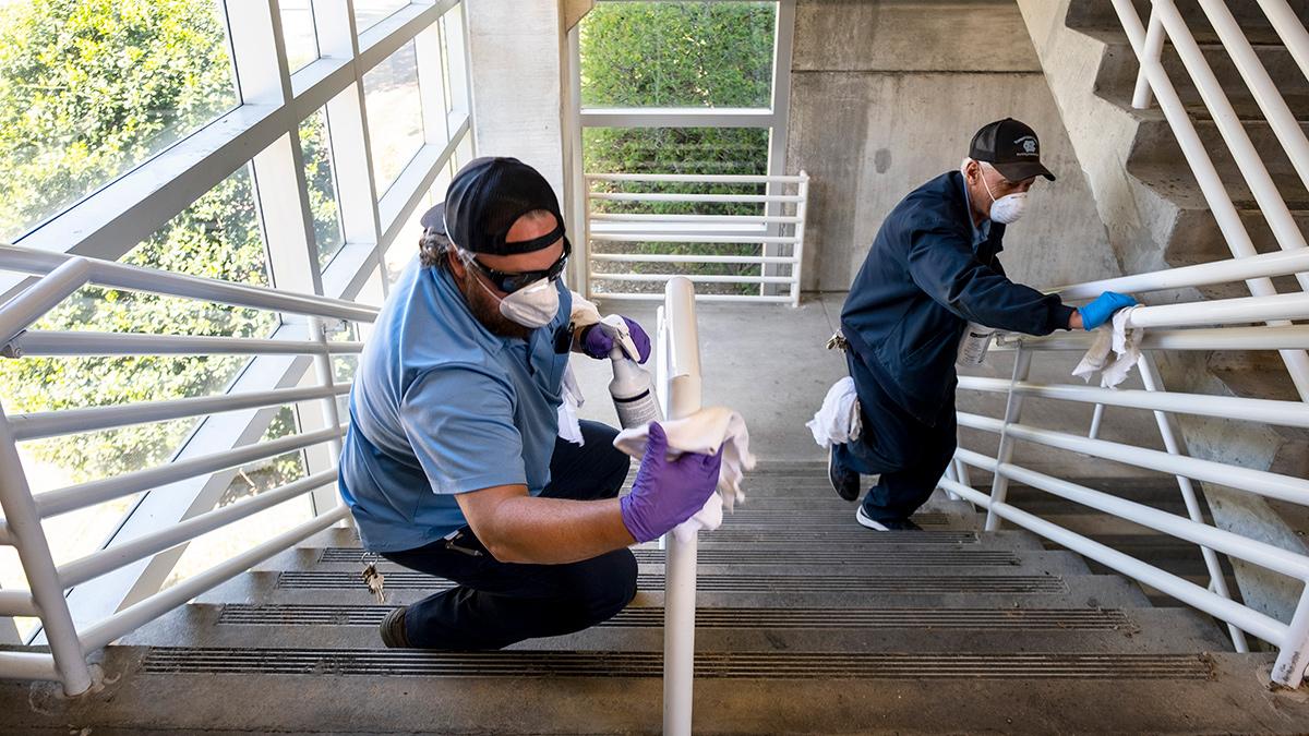 Workers clean stair railings
