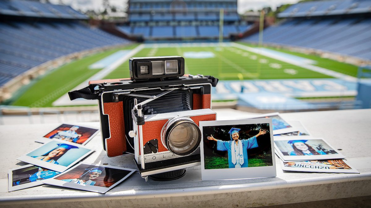 A polariod camera in Kenan Stadium with photos around it.