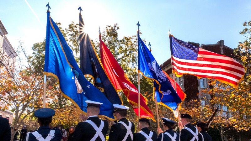 Flags of various military branches being held by ROTC Cadets.