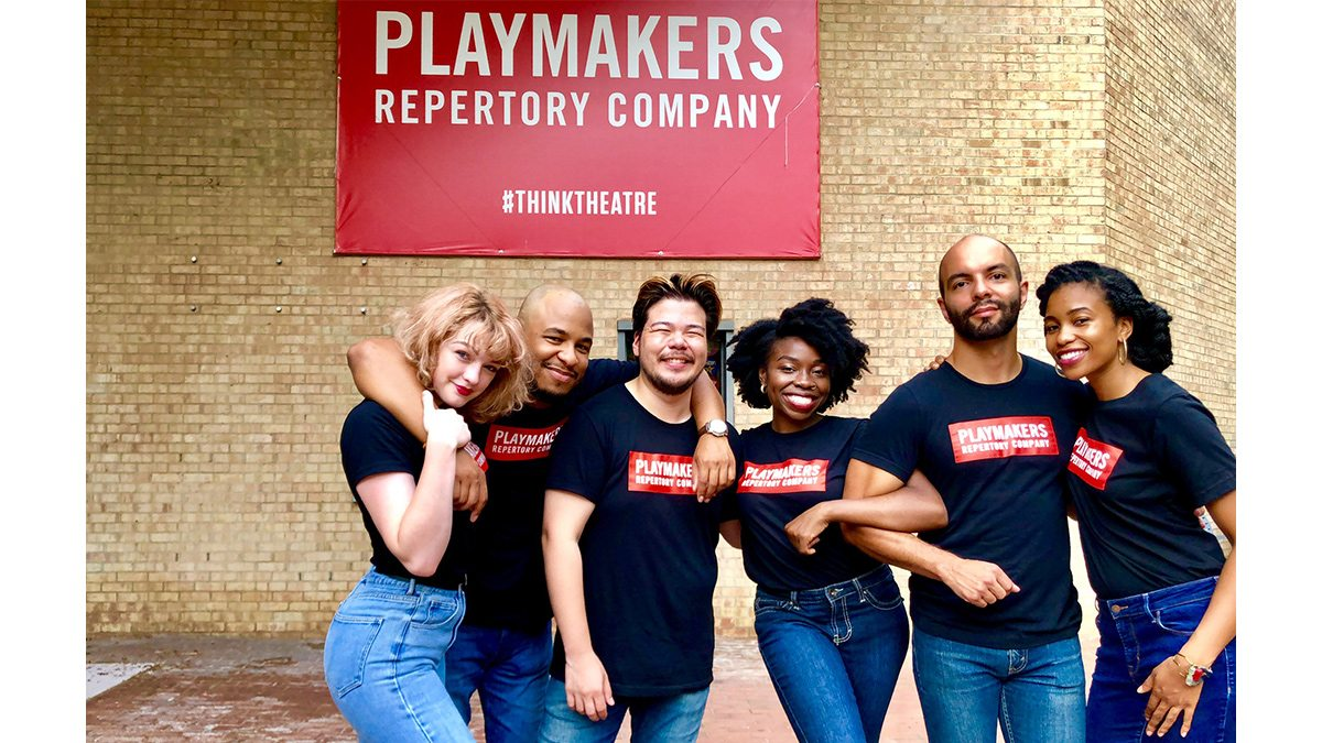 Students posing for a photo in front of PlayMakers Theater.