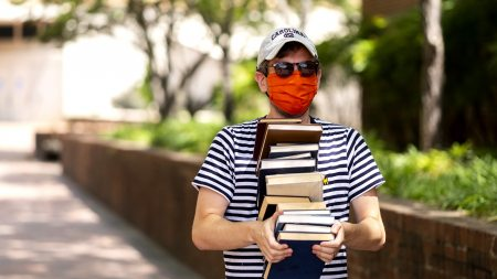 A student wearing a mask carries books.