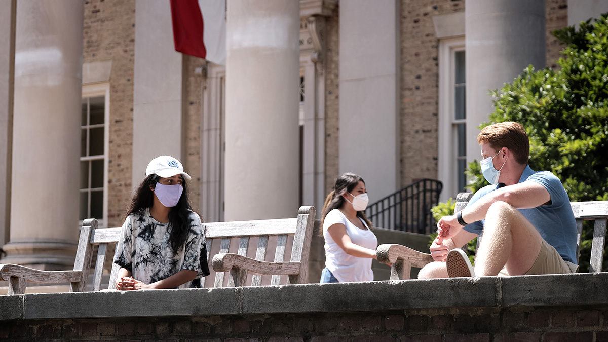 Students wearing masks in front of South Building
