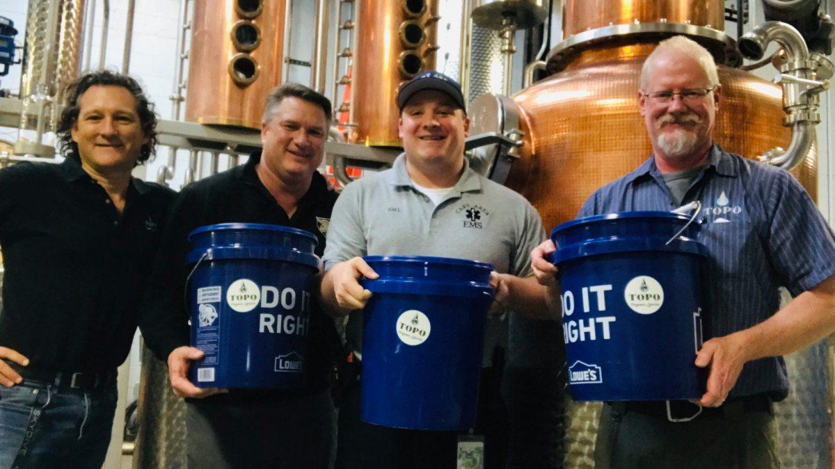 Four men hold blue buckets near distillery equipment