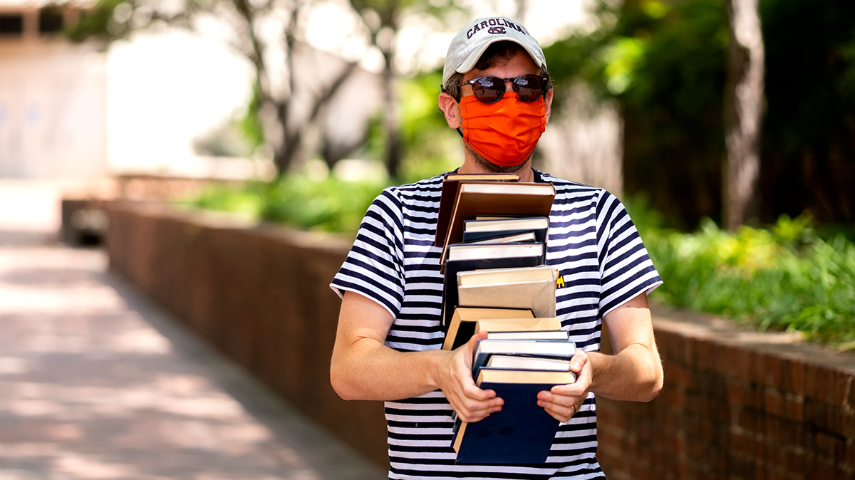 A man wearing an orange mask carries a stack of books on campus.