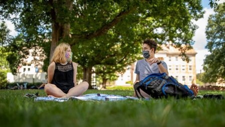 Students sit near each other on campus.