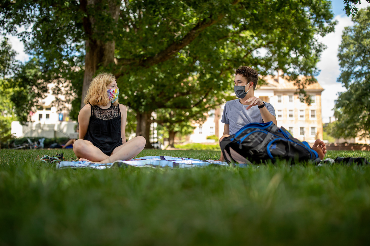 Two students sit on Polk Place.