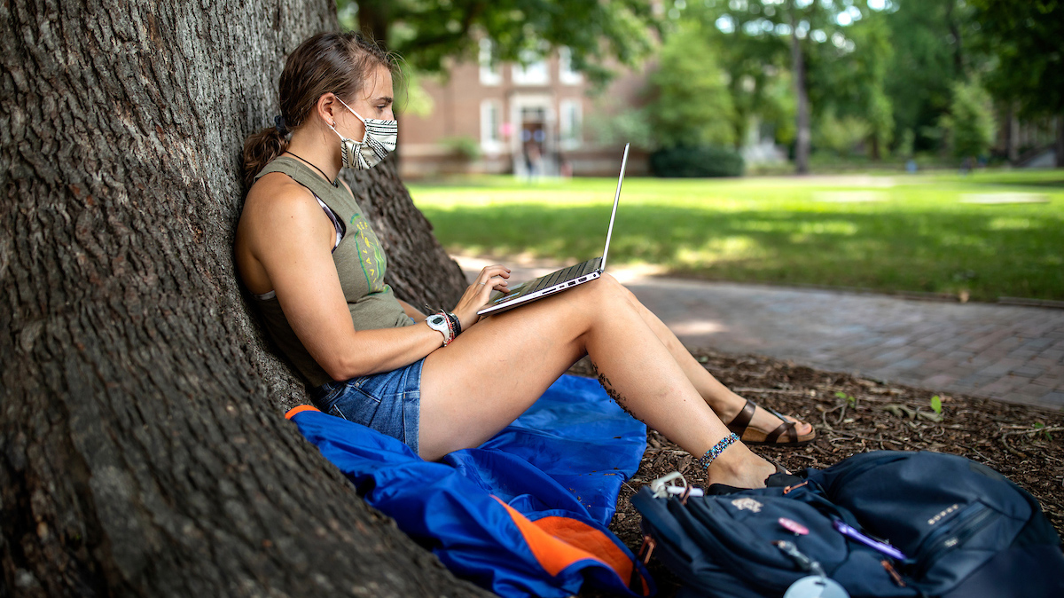 A student works on her laptop while sitting against a tree.