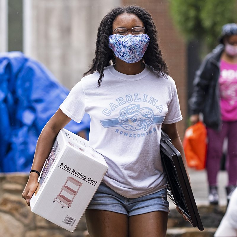A student carrying boxes as she moves into a residence hall.