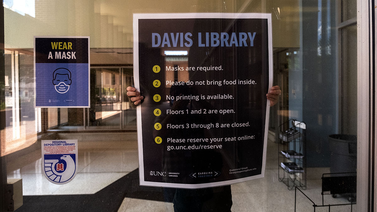 A person puts a sign of community standards in a library window.