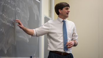 Brad Staats talks near a chalkboard while teaching a class.