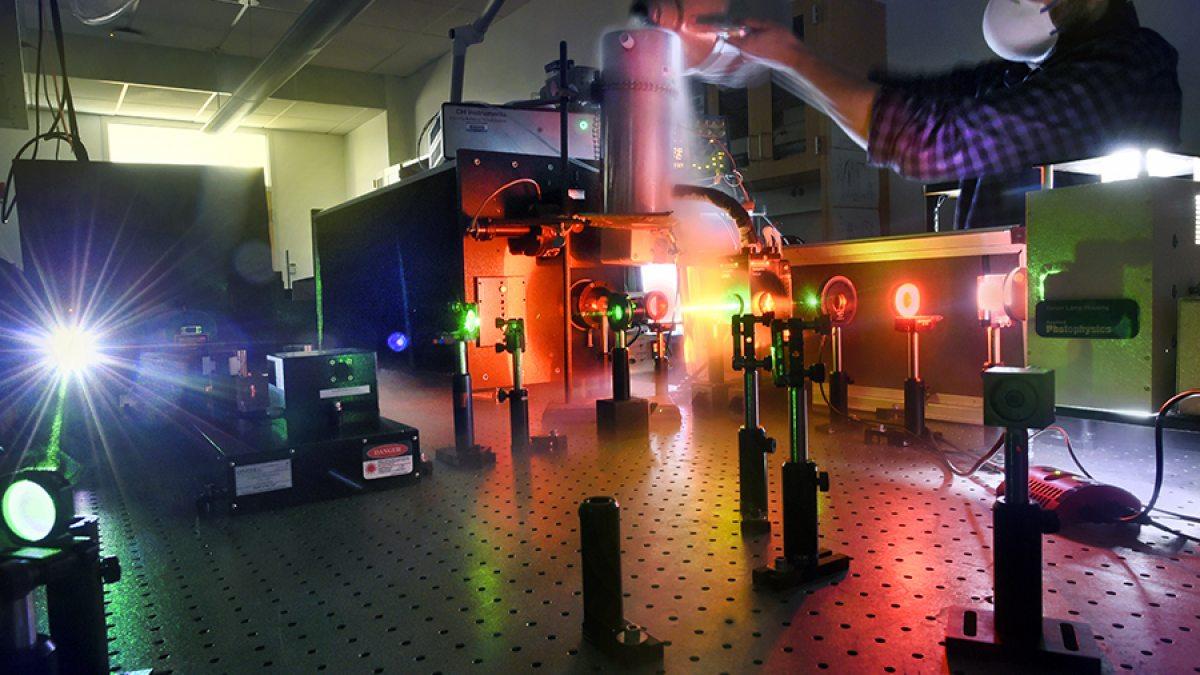 An experience using lasers is conducted on a table.