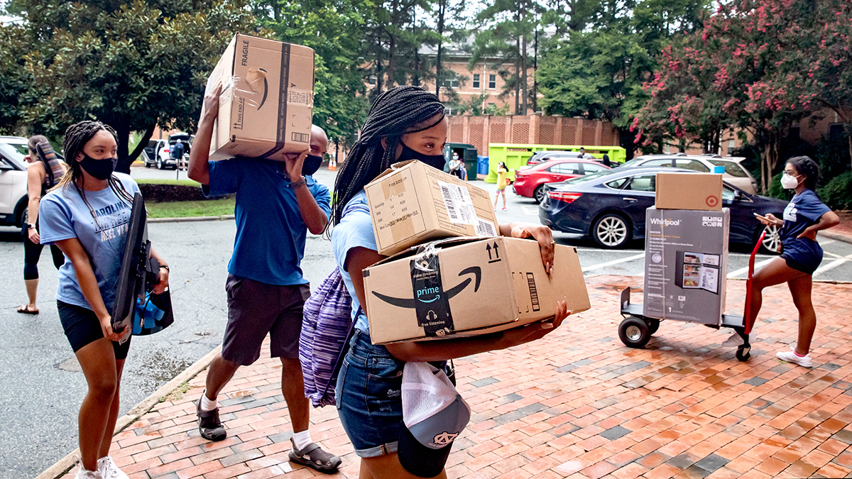 A student carries several cardboard boxes during move in.
