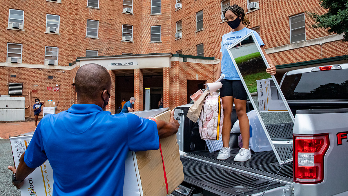 A female student unloads the back of a pickup truck during move in.