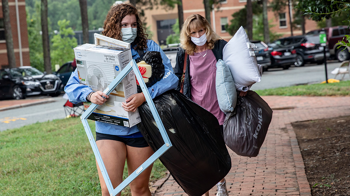 Two women carry several boxes during move in.