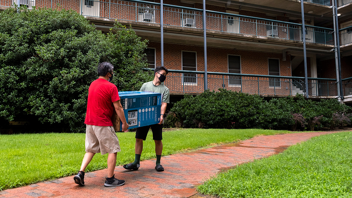 Two men carry a minifridge during move in.