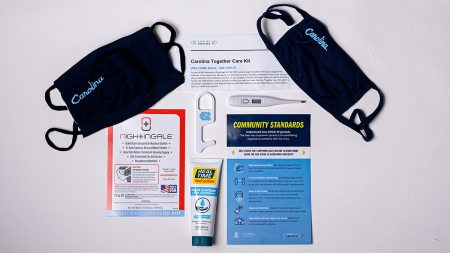 Two masks, a bottle of hand sanitizer, a thermometer and pieces of paper with health instructions on a table.