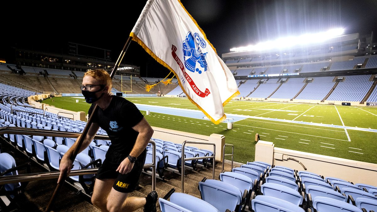 Student carries flag and runs up stadium stairs