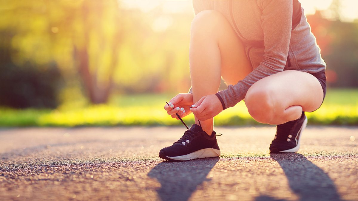 A woman runner ties her running shoes.
