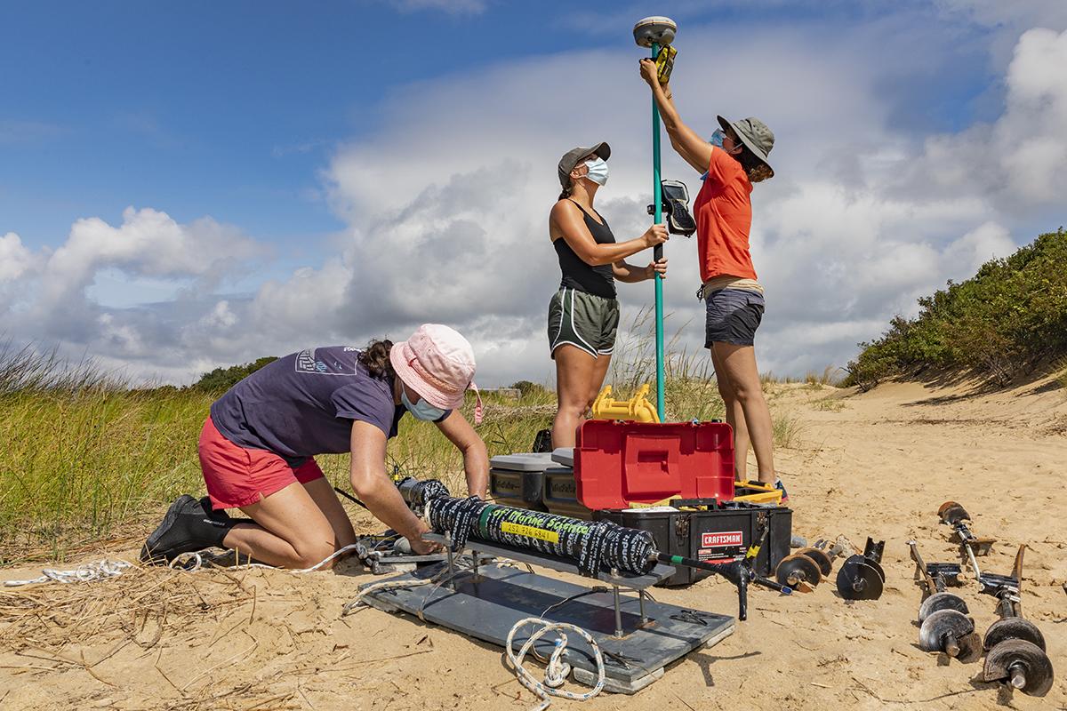Three reseachers prep equipment on the beach.