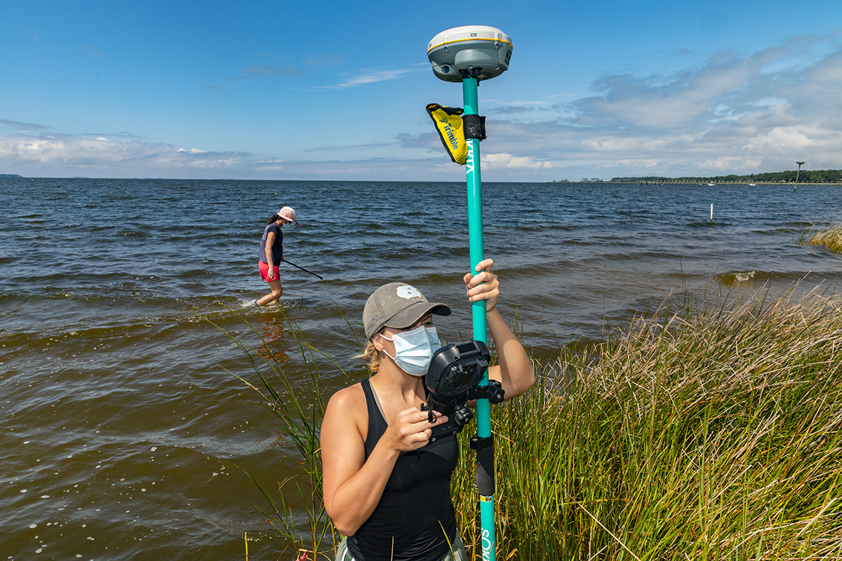 Joey Carter uses a GPS device to measure wave height from the water.