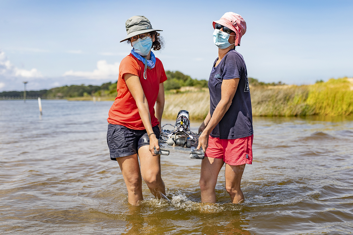 Two researchers carry a large piece of equipment into the ocean.