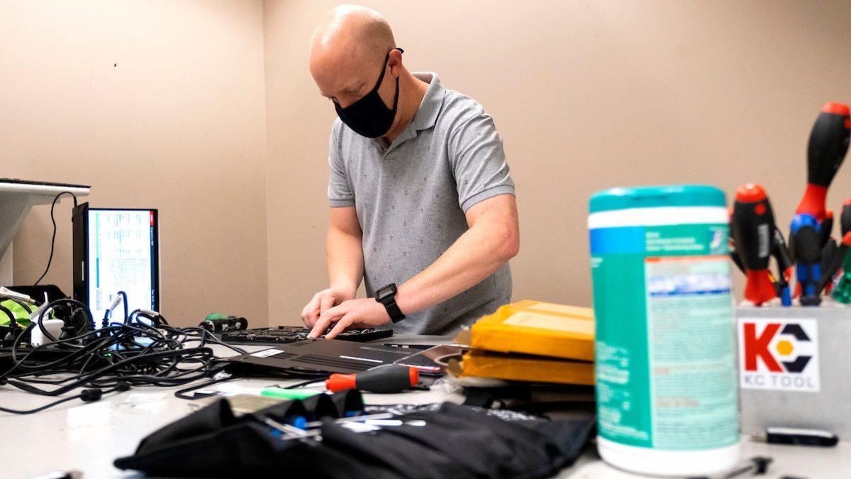 A man repairs a laptop.