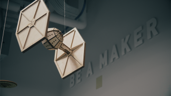 A wooden model of a Star Wars TIE figher hangs from a ceiling.